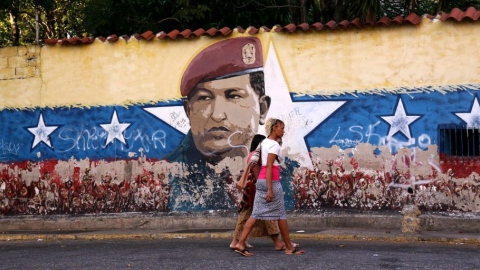 Women walk past a mural of Hugo Chávez on January 31, 2019 in Caracas, Venezuela. (Edilzon Gamez / Getty)